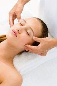 Closeup of a beautiful young woman receiving face massage